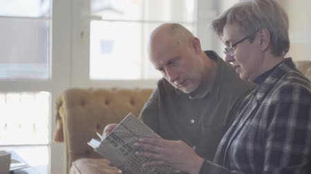 dizendo : Old couple, man and woman, sitting on the sofa with a book and talking and smiling to each other. Male is bald and female have short grey hair. Happy loving family. Stock Footage
