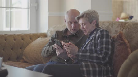 memories photos : Senior couple sitting on the big sofa and bald man showing photos in the mobile phone for his woman with short grey hair. Family are very happy and smiley looking at each other with love and tenderness. Stock Footage