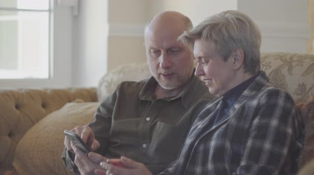 remember : Senior couple sitting on the big sofa and bald man showing photos in the mobile phone for his woman with short grey hair. Family are very happy and smiley looking at each other with love and tenderness. Stock Footage