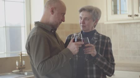iyi olmak : Old couple stand in the kitchen with glass of wine in them hands, woman try to calm down and relax her man telling him that all will be good. Loving caring wife. Family concept.