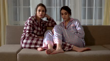 kanapa : Pretty twin sisters in pajamas are sitting on the sofa and choosing what to watch on TV in the living room.