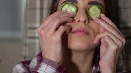 chill out : Portrait of beautiful young woman in pajama making eye mask from cucumbers in cozy evening, chilling and relaxing