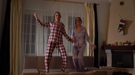 piada : Playful adult twin sisters in pajams jumping on the couch in a cozy living room and having fun like in childhood