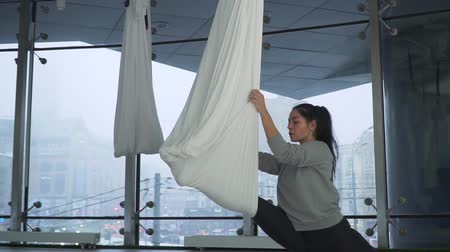 gravidade : Beautiful woman turns over in the air holding on yoga hammock in studio. Many white empty hammocks around. Modern cityscape behind window. Vídeos