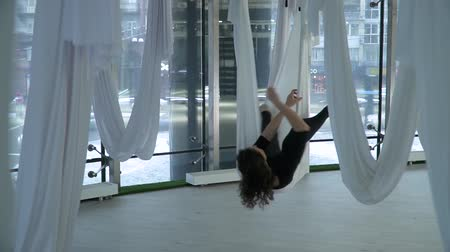 hatha : Beautiful woman hovers in hammock for yoga taking different poses in studio indoors. Many white empty hammocks around. Modern cityscape behind the window. Athletic girl practicing aerial yoga. Camera moves left Stock Footage