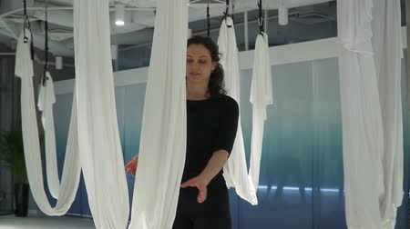holding onto : Beautiful woman turns over holding onto hammock for yoga in studio indoors. Many white empty hammocks around. Beautiful cityscape behind floor-to-ceiling window. Slow motion