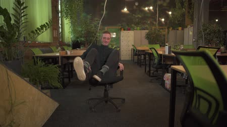 fool : Cheerful young man in glasses spinning on an office chair in modern office decorated in green tones. Office worker having fun alone