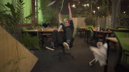 tons : Young positive man in glasses spinning on an office chair and throwing up papers in modern office decorated in green tones. Office worker having fun.