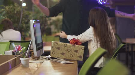 tezgâhtar : Pretty woman with long hair getting present from her colleague and hugging him at office. Unrecognizable man made a surprise for his female co-worker, gave her big box with ribbon on it. Good relationship at work Stok Video