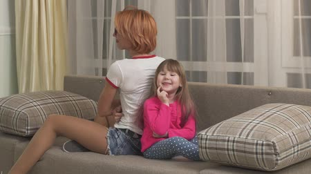 терпение : Mother and daughter spending time at home, having fun together. Little girl and her young mom sitting on the sofa back to back, woman tickles her child. Kid laughing looking in camera. Generation of women. Slow motion Стоковые видеозаписи