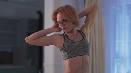 милый : The girl shows her pumped belly press. Cropped photo of young attractive woman with short red hair in glasses puts on sport top at home. Стоковые видеозаписи