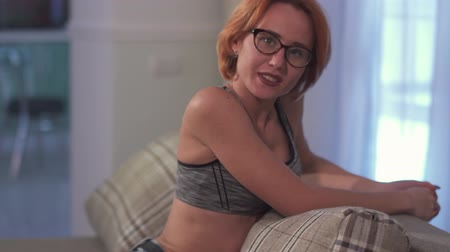 genç yetişkinler : Portrait of young attractive woman with short red hair in glasses sitting on the comfortable sofa at home. Stok Video