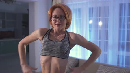 жизнь : The girl shows her pumped belly press. Cropped photo of young attractive woman with short red hair in glasses puts on sport top at home. Стоковые видеозаписи