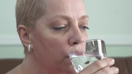nyel : Portrait of mature female with short blond hair who drinking water from the glass. Womans health care. Stock mozgókép
