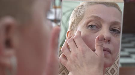 çene : Mature woman applying facial cream on the face while looking at mirror. Consept skin care.
