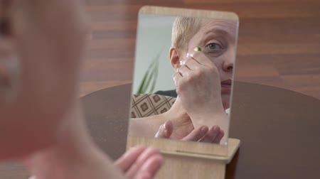 toner : Beautiful elderly woman looking at the mirror and rubs face with a slice of cucumber at home. Cosmetic procedure skin care. Emotion concentration of choice. Concept skin care.