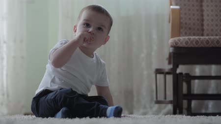 go away : Cute baby sitting on the floor on fluffy carpet playing alone. The boy gets up. The unrecognizable woman comes, picks up the child and goes away. Concept of parenting