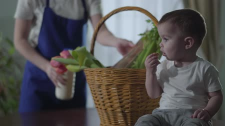 get out : Unrecognized girl wears a blue apron. A little boy sits near the basket on the table and eats