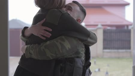 obránce : Strong young man wearing military uniform came home and happy embracing his beautiful cheerful wife on the background of street