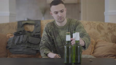 traumatic : The man in military closes opening beer bottle sitting at home on the sofa. An unhappy man returns from the military service. The soldier has problems, he is drinking alcohol to soothe the pain Stock Footage