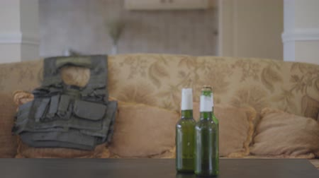 traumatic : Three beer bottles standing on the table in front of the old sofa with bulletproof vest lying on it. The soldier has problems, he is drinking alcohol to soothe the pain