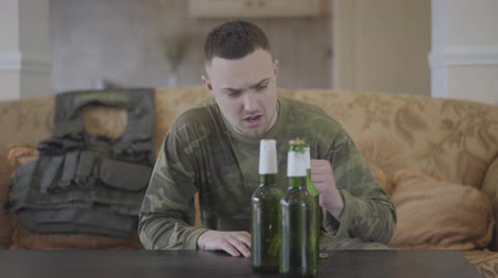 homecoming : Three beer bottles standing on the table in front of the old sofa with bulletproof vest lying on it. The man in military closes sits on the couch and drinks beer. An unhappy man returns from the military service. Soldier is drinking alcohol