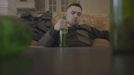 melankoli : Sad young guy in military uniform returning after the army drinks from grief a lot of beer sitting in the living room Stok Video