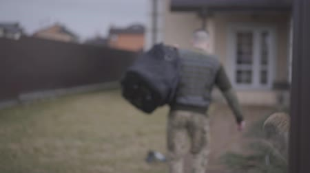 bulletproof : The young man in the military closes with big bag entering the gate and walking toward the big house. A man returns from the military service home. Leaving from war. Back view