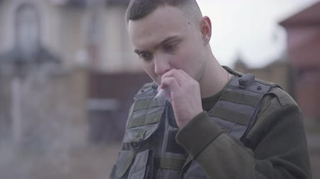 bulletproof : Close up face of the soldier smoking cigarette in front of the big house. The man has a problem, he is unhappy and trying to soothe the pain. Bad habit. A man returns from the military service home