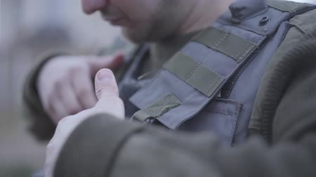 khaki : Unrecognizable young soldier putting on his light bulletproof vest close up. The man preparing for the war action. Military and special forces equipment