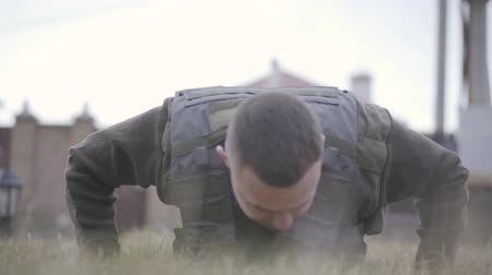 bulletproof : Young soldier falling down and wrunging out from the floor in bulletproof vest close up. The man preparing for the war. Military and special forces equipment Stock Footage