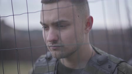 hnědožlutý : Close up face of the soldier standing in the bulletproof vest behind the net. A man is in the military service. The warrior preparing for the war. Military and special forces equipment