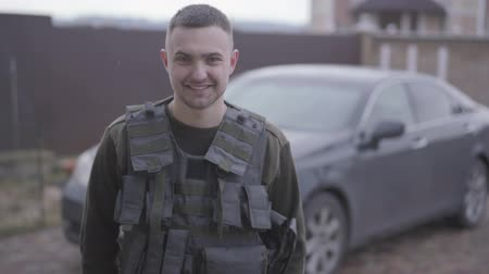 bulletproof : The young happy man in military closes in the bulletproof vest standing in front of his car in the yard at home, smiling. A man returns from the military service home. Leaving from war