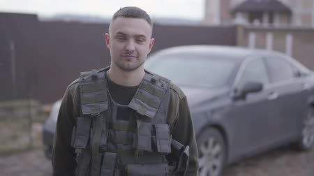 defending : Portrait of young brave military man staying and smiling on the street in uniform on the background of car