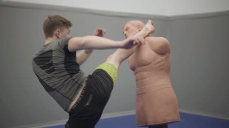 direkt : The young confident man beats the dummy with his fist in the gym. Young confident boxer hitting dummy of human body shape in the gym. Martial art concept. Slow motion