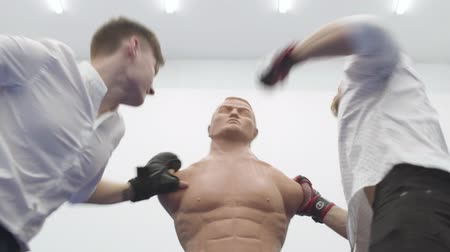 manichino : Two aggressive blond men punch a bob box mannequin in the gym