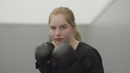 инструктор : Young blond girl panching on camera in boxing gloves. Martial arts. Training. Стоковые видеозаписи