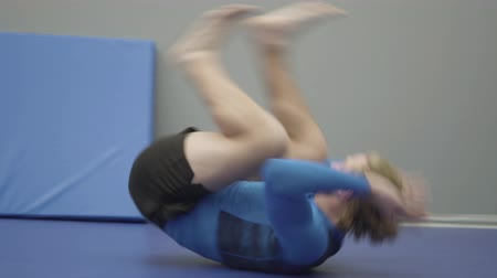 beardie : Confident bearded man in blue sportswear rolls forward in the gym close up. The beardie doing warm-up before training. The camera follows the athlete