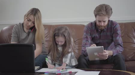 lack : Little girl sitting between mother and father drawing with colored markers. Young woman typing on her laptop talking by cell phone, bearded man working on his tablet. Concept of busy parents, modern family with gadgets