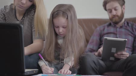 odpowiedzialność : Little cute girl with long hair drawing with marker, sitting at the table on the sofa. The mother is working by laptop, father scrolling the screen of his tablet. Concept of busy parents, lack of communication Wideo