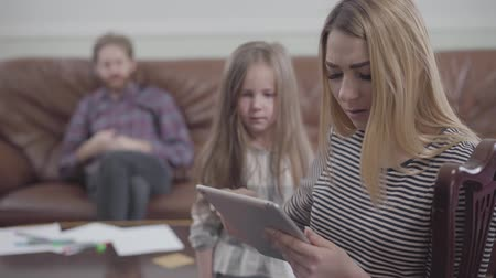 получать : Portrait of pretty blond woman sitting with tablet in hands close up. Little girl trying to get attention of her mother while father sitting on the sofa on the background. Mother addicted to gadgets. Lack of live communication