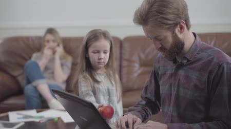 ignoring : Portrait of the bearded man working with tablet close up. Little girl unsuccessfully trying to give the man the apple while mother sitting on the sofa on the background. Young man addicted to gadgets. Lack of live communication Stock Footage