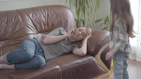 focus pull : Pretty blond woman lying on the leather sofa talking by cell phone. Little girl pulls her mother hand, she needs attention, but woman continues the conversation. Lack of live communication Stock Footage