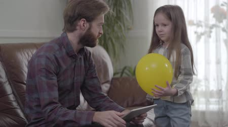 irritação : Portrait of concentrated bearded man working with his tablet close up. Little girl unsuccessfully trying to give the man the balloon but irritated father shows her that he is busy. Child is sad. Young man addicted to gadgets Vídeos