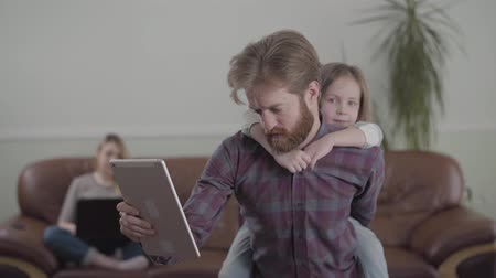 juntar : The bearded man working with tablet, involved in his job close up. Little sad girl sits on fathers back, trying to get attention. The mother on the sofa with laptop on the background. Lack of live communication