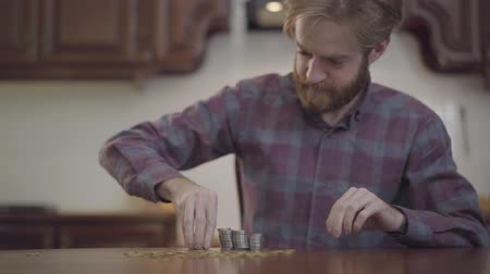 beardie : Portrait of bearded man sitting at the table in the kitchen counting his money. Beardie in checkered shirt stacks silver coins. Concept of wealth and poverty.