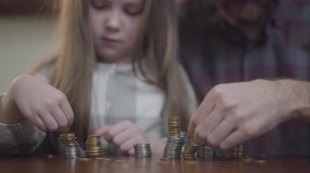 cent : Unrecognizable man in shirt and little concentrated girl sitting at the table close up counting coins. Father and daughter making stacks from gold and silver coins. The dad teaching kid economy. Money saving concept