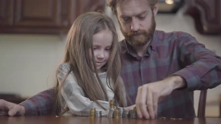 empilhamento : Portrait of bearded man sitting at the table in the kitchen with his cute daughter counting money. Beardie in checkered shirt stacks silver coins, little girl helps him. Concept of wealth and poverty Vídeos