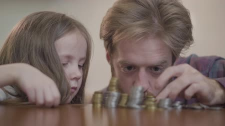 beardie : Portrait of bearded man sitting at the table in the kitchen with his cute daughter counting money. Beardie in checkered shirt stacks silver coins, little girl helps him. Concept of wealth and poverty Stock Footage