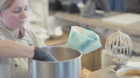 brulee : Female baker in uniform putting just cooked vanilla mixture in a special bag for the cream to decorate the cake Stock Footage